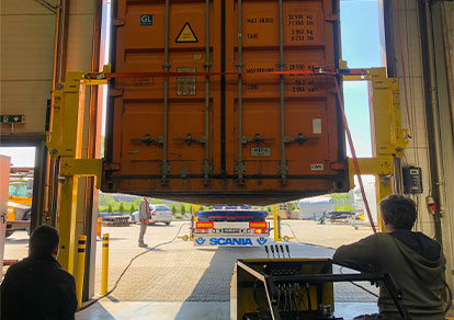 The truck drives to the loading of the container lifted by lifting jacks